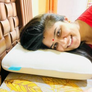 smiling woman with a red dot on her forehead posing on a levitex in her bed
